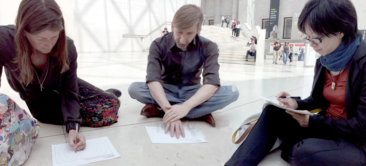 Students sit on the floor and take notes about what they are hearing.